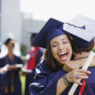 Smiling graduates hugging outdoors