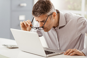 Businessman working at office desk, he is staring at the laptop screen close up and holding his glasses