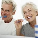Senior Couple In Bathroom Brushing Dental Implants to whiten teeth and help prevent tooth decay.