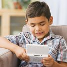 Hispanic boy playing handheld video game on sofa