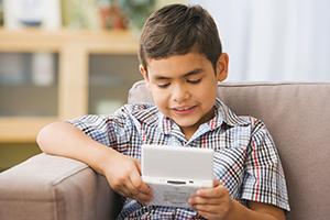 Hispanic boy playing handheld video game on sofa