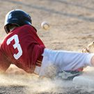 Baseball player sliding into third base causing dust to fly. This could cause retina damage from disease and injury.
