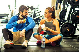 Young couple at gym choose healthy snacks after exercising.