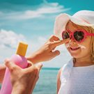 Mother putting sunblock on daughter's face at the beach.