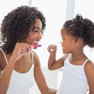 Pretty mother with her daughter brushing their teeth.