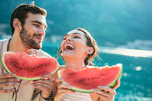 Cheerful couple holding slices of watermelon.