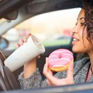 Woman having a donut and drink while driving a car.