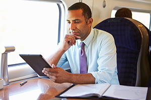 A businessman using a tablet on a train