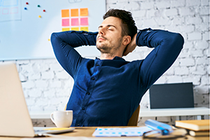 Businessman relaxing at work with hands behind head, eyes closed and a coffee. No tinnitus symptoms present.