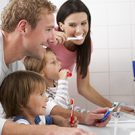 A family brushing their teeth in the bathroom.
