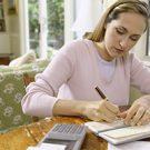 Woman sitting at table writing a check