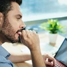 Anxious Businessman Biting Nails Working With Laptop Computer In Office