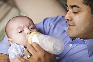 Hispanic man feeding baby before the newborn undergoes hearing tests.