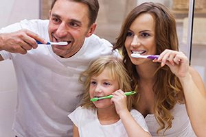 Family shown brushing their teeth which helps lower dental costs.