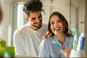Young couple at bathroom sink, laughing and brushing teeth. They are discussing the best ways to look for a dentist.