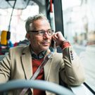 Elderly businessman travelling by bus in city.