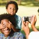 Woman photographing husband and son in park with digital camera.