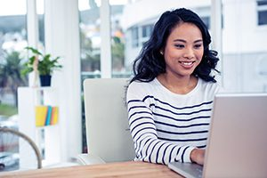 Smiling Asian woman using laptop in office