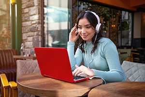 Young girl on laptop wearing headphones.