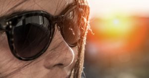 The face of a young girl in sunglasses, sun shining in background.