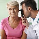 Doctor examining ear of senior woman to see if she has an ear infection.