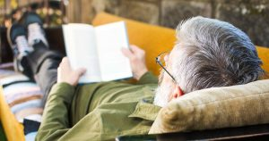 Senior man reading a book in the backyard.