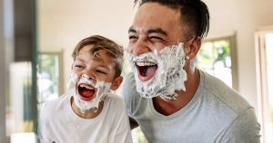 Father and son having fun while shaving in bathroom.