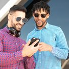 Two young men using a cell phone.