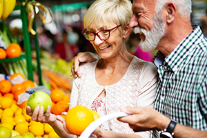 Senior couple shopping vegetables and fruits on the market.