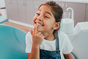 Small girl smiling and pointing to teeth while sitting in a dentists chair.