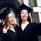 Two women enjoying graduation ceremonies.