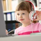 Little girl is getting ready for school, wearing headphones and using a computer.