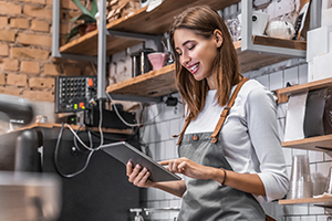 Smiling coffee shop owner standing on her workplace near counter and using digital tablet.