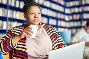 African American woman having coffee while on her laptop at the library.
