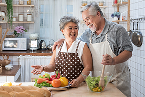Senior couple laughing and cooking together in the kitchen.