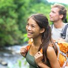 Couple hiking with backpacks near water.