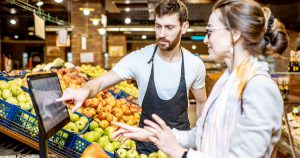 Male employee helping female customer in produce section.