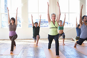 Men and women taking a yoga class as a way to look out for their employee health and well-being.