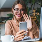 Female looking at her phone and smiling, reading about eye care tips from optometrists.