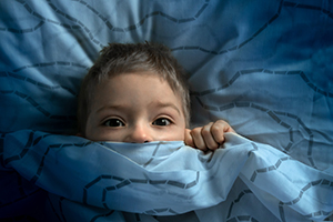 Small boy under the covers afraid of the dark.