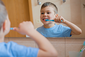 Young boy standing in front of the mirror brushing his teeth.