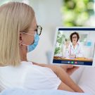Sick woman in face mask talking to doctor on tablet.