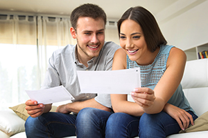 Happy young couple viewing a loan statement on their couch at home.