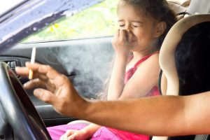 Young girl riding in car covering nose from breathing in cigarette smoke.