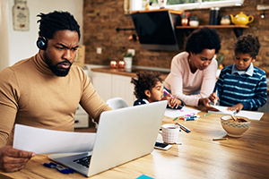 African American working father using laptop while mother is homeschooling their children.