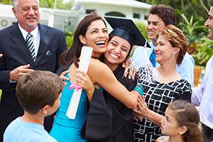 Hispanic student and family celebrating graduation.
