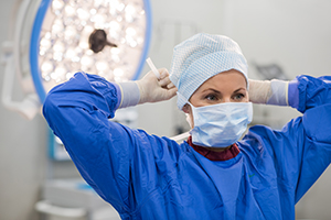 A young female doctor tying her mask and preparing for surgery.