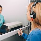 An audiologist doing a hearing test on a female patient.