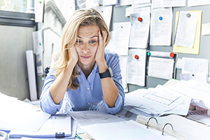 Stressed woman sitting at desk in office surrounded by paperwork.