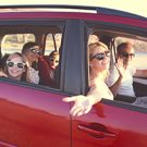 Happy family with daughters in the car going for a drive.